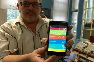 Benjy Blatman, the attendance coordinator at P.S. 125, shows the Kinvolved app on his mobile phone.