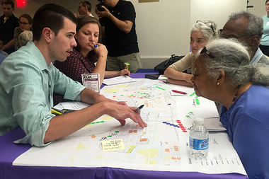 Residents mark streets on a map to show where they think the Brooklyn-Queens Connector (BQX) should stop in Brooklyn at a public meeting held Monday at St. Francis College.