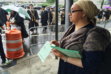 An organizer passes out fliers at the City College commencement ceremony Friday to call for more funding to the city's public college system.