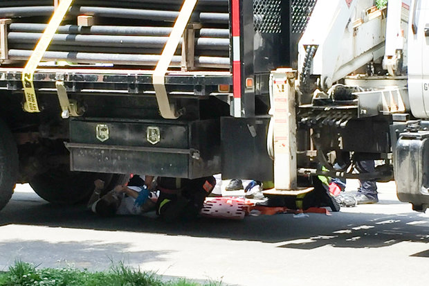A cyclist hit another bike and fell under the flatbed truck Thursday morning, witnesses said.