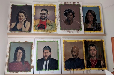 A sampling of the portraits painted for the Free Portrait Project: Crown Heights hangs on the wall of the studio of Rusty Zimmerman, located at 1000 Dean St.