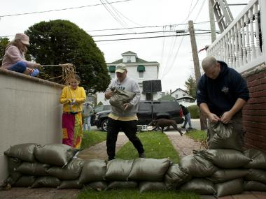 Two families who live side by side install a wall of sandbags to protect their basement as Hurricane Sandy approaches on October 28, 2012 in the Rockaway Beach neighborhood of the Queens borough of New York City. New York City Mayor Michael Bloomberg announced a mandatory evacuation on low-lying coastal areas of the city. Sandy, which has already claimed over 50 lives in the Caribbean is predicted to bring heavy winds and floodwaters to the mid-Atlantic region.