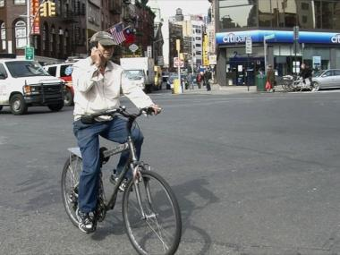 A biker on his cell phone crosses Chatham Square in Chinatown, a major intersection in New York where five major streets intersect.