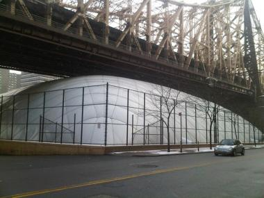 The Sutton East Tennis Club's bubble under the Queensboro Bridge. Softball players were granted permits to play at the Oval for the summer, overturning an agreement to operate the bubble year-round.