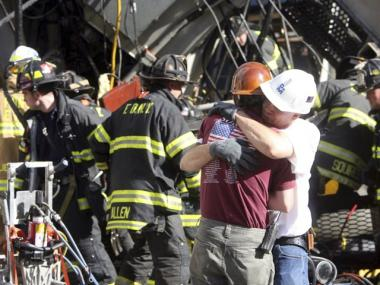 Construction workers embrace as rescue crews work at the scene of a crane collapse on New York's Upper East Side on May 30, 2008.
