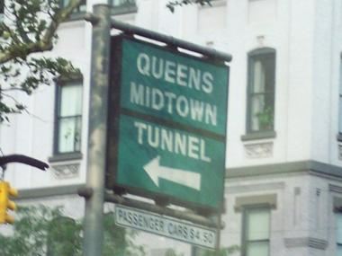 A sign points to the Queens-Midtown Tunnel.