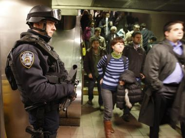 An NYPD counterterrorism officer watches commuters entering the subway at Grand Central on Monday, March 29, 2010. The Department of Homeland Security announced cuts to New York's anti-terror funding in May.