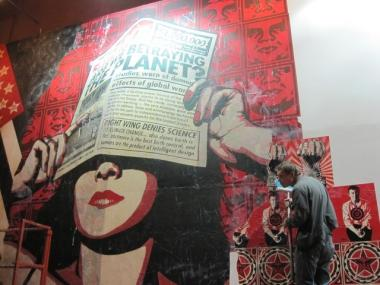 Street artist Shepard Fairey work on his latest project on E. Houston Street and the Bowery Tuesday night.