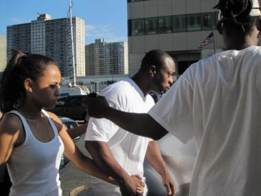 Andre Muller, father of slain high school football star Isayah Muller, was ushered out of the Bronx Criminal Courthouse after being arraigned on assault charges on June 28, 2011.