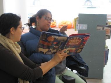Janielle Fermaint reads a book inside the BPC Library with help from Cathy Valladares, of Job Path.