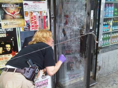 Crime scene detective looks for fingerprints on the bodega's front door.