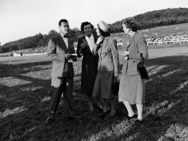 The late billionaire Paul Mellon and his wife Rachel 'Bunny' Mellon talk with two unidentified women at the Rolling Rock race meet, October 5, 1946.