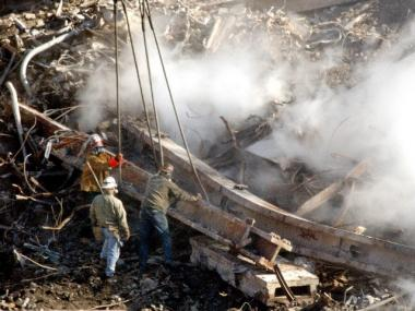 Workmen attach cables from a crane to a steel beam at the smoldering remains of the World Trade Center towers in lower Manhattan, Monday, October 8, 2001.