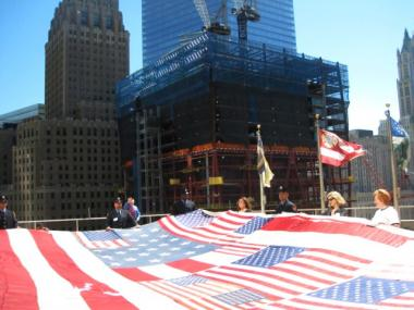 The National 9/11 Flag, with One World Trade Center, formerly known as the Freedom Tower, standing behind.