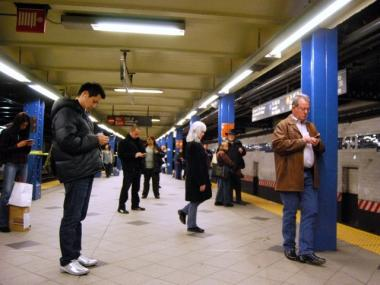 Straphangers use their mobile devices on the subway platform.  Cellular and WiFi service is being planned for underground.