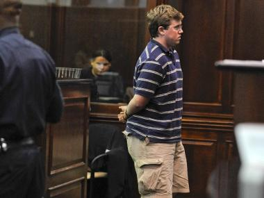 Michael Enright, 21, in handcuffs at his arraignment.