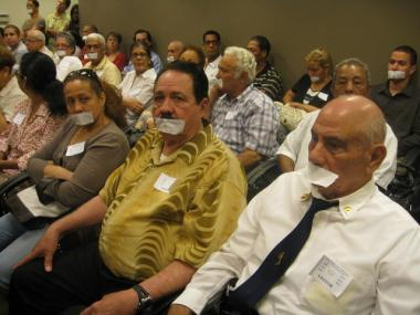 Antonio Abreu, 68, and Desiderio Matos, 76, both of Washington Heights, wore white tape over their mouths to symbolize the fact that they were not allowed to speak at the hearing.