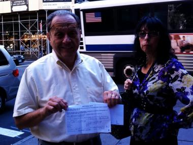 Sol Szmulewicz, with wife Laureen, shows off a referral card directing him to a new polling location after he discovered his name wasn't on the list.