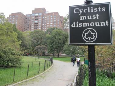 The parks department recently posted signs telling cyclists to dismount on this Riverside Park path, but cyclists say the path is an official bike route on city maps.