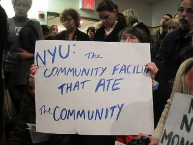 Diane Welton, a resident of Greenwich Village for 40 years, held up a sign in protest at the Community Board 2 Joint Landmarks and Institutions meeting Monday.