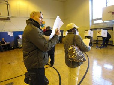 A Harlem voter inspects his ballot Tuesday morning.