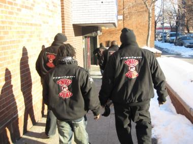Operation SNUG outreach workers with their identifying jackets outside the New York Mission Society's Minisink Townhouse on 142nd St. and Lenox Avenue.