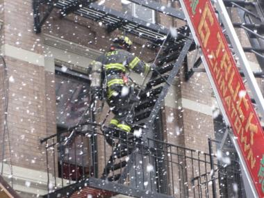 A firefighter checks the Ludlow St. building in heavy snow.