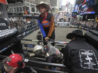 McKennon Wimberly, bottom center, prepares to rides Little Mr. T in the Professional Bull Riders competition, Friday, Oct. 15, 2010 in Times Square.
