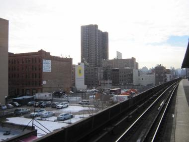 Metro-North train tracks pass over Park Avenue in East Harlem, dotted with parking lots and undeveloped space.