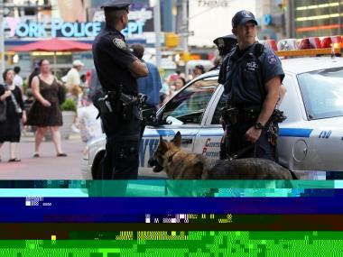 NYPD Detective Bonomo (R) and police canine Hunter keep watch in Times Square June 21, 2010 in New York City. Accused Times Square bomber Faisal Shahzad pleaded guilty on June 21 to all terror and weapons charges.