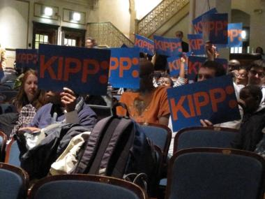KIPP supporters hold up signs at a Panel for Educational Policy hearing.