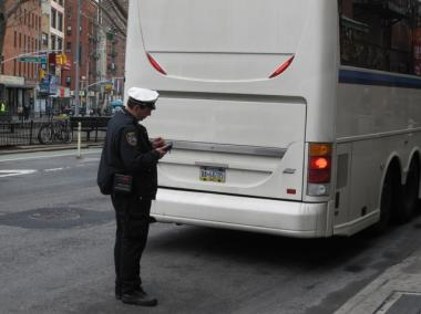 A police officer inspects a bus on Allen Street after two tour buses crashed, killing 17 people.