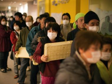 Displaced earthquake victims line up at a evacuation center March 22, 2011 in Kesennuma, Japan. The country is struggling to contain a potential nuclear meltdown after the Fukushima Dai-Ichi nuclear plant was seriously damaged from the quake.