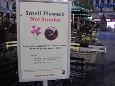 A sign mounted in Greeley Square advertises the smoking ban in city parks.