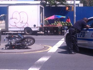 Cops examine the aftermath of a crash that injured a motorcyclist at W. 146th Street and Adam Clayton Powell Blvd.