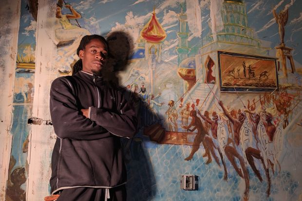 Omar Hardy stands in front of a mural painted inside the Black Lady Theatre in Crown Heights, which he is trying to restore with his father, Clarence.