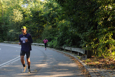 Joggers run on East Drive in Central Park, where a female runner was nearly raped on Monday night, police said.