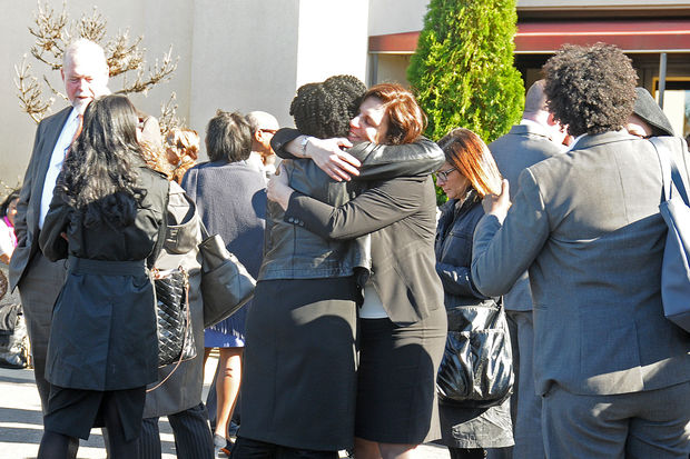 Mourners embrace outside a wake for Ken Thompson in East New York Friday, Oct. 14, 2016.
