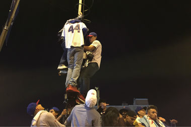 Cubs fans climb a Chicago Police camera across the street from John Barleycorn.