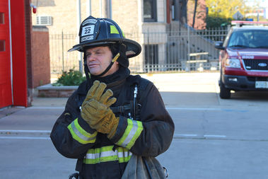 U.S. Rep. Mike Quigley dons firefighter gear at the Armitage firehouse.