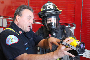 Capt. Ronald Kitowski shows U.S. Rep. Mike Quigley a heat-sensing camera used to find people or the source of a fire in a smoke-filled building.