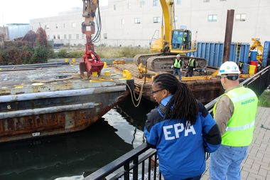 An EPA official and a contractor watch the first day of debris removal from the Gowanus Canal waterfront walkway behind the Whole Foods on Third Avenue and Third Street.