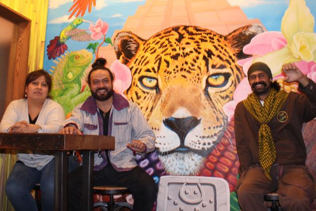 From left to right, the proprietors of Cafe Ix, Brenda Castellanos and Jorge Cardenas, sit in front of a mural of a jaguar (for which the cafe is named) with the painting's creator, the muralist M.C.H.E.