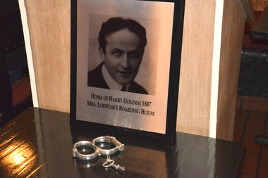 Houdini's broken handcuffs from one of his escape tricks sit next to the plaque that will be placed on the facade of 244 E. 79th St.