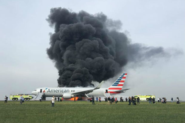 A harrowing scene played out at O'Hare Airport Friday afternoon after an American Airlines flight caught fire on a runway, forcing 170 people to flee the plane on inflated slides as huge flames and thick black smoke poured out.