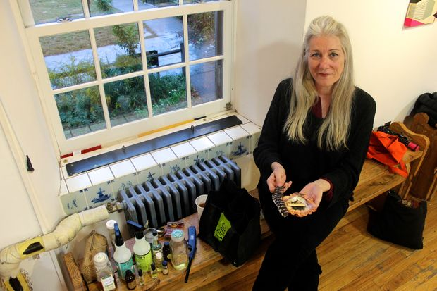 Cathy Towle, a professional psychic medium who performs house cleansings to rid properties of troublesome spirits, with some of the gear she uses in her work.
