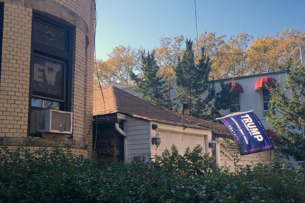 "Michael Byrnes posted a cardboard sign with the word ""Ew"" and arrow pointing to a Donald Trump flag flying outside the garage next to his apartment building."