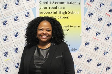 Andrea Piper is the principal at the ACORN Community High School in Crown Heights. Behind her, pledges by students to earn a certain amount of credit each year decorate a hallway in the school.