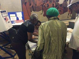 Poll Coordinator Brenda Anderson, left, helps voters at the Drew-Hamilton Houses, located at200 W.143rd St.