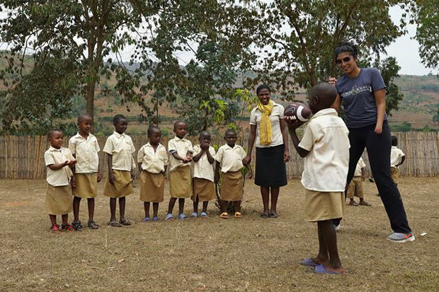 Building a school in Africa, Priya Shah shows students how to play football.